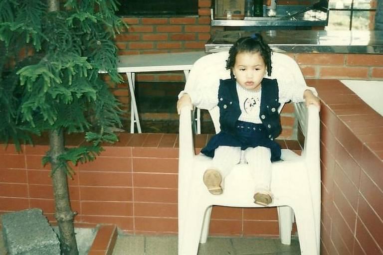 Caroline, quando pequena, ao lado do pinheiro, pelo qual hoje tem carinho