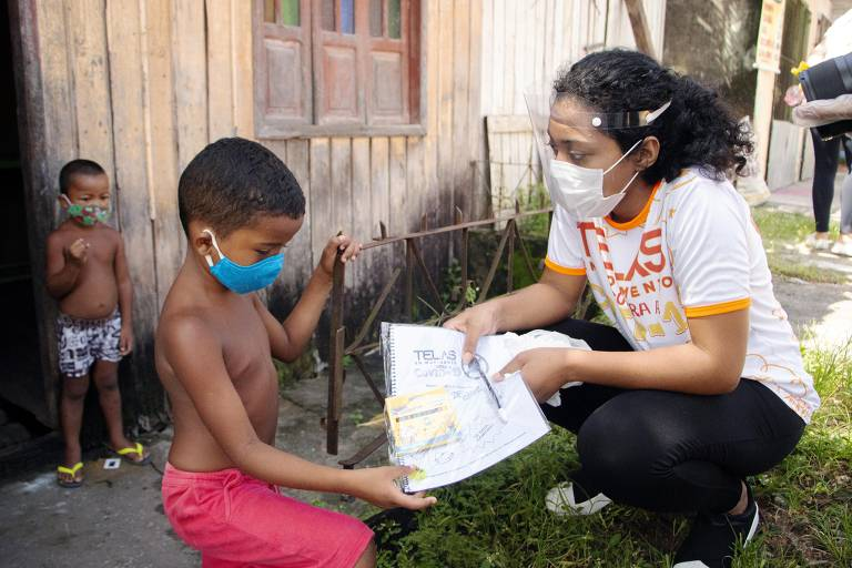 Na foto, Joyce Cursino explica a uma das cem crianças que receberam kit de arte educação como utilizar o material para criarem os seus heróis para combaterem a Covid-19