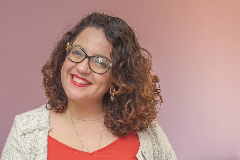 Mulher branca sorrindo, cabelos cacheados soltos, veste calsa e blazer bege e blusa laranja, está de pé em um ambiente de escritório