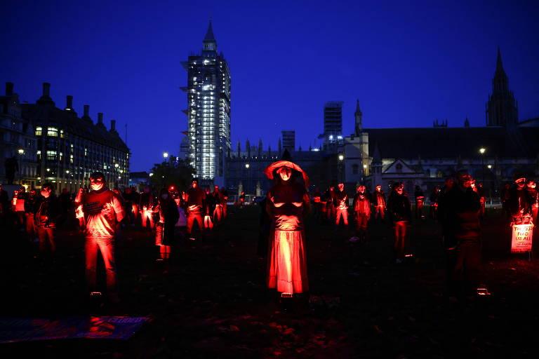 Pessoas com fantasias iluminadas em praça, à noite