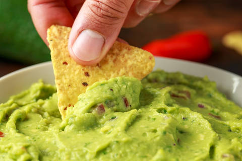 Man hand is picking some guacamole dip with nachos chip. Healthy Vegan, Vegetables food