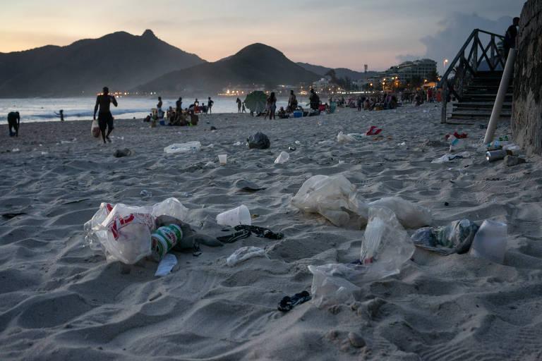 Lixo espalhado pela areia da praia no fim do dia.