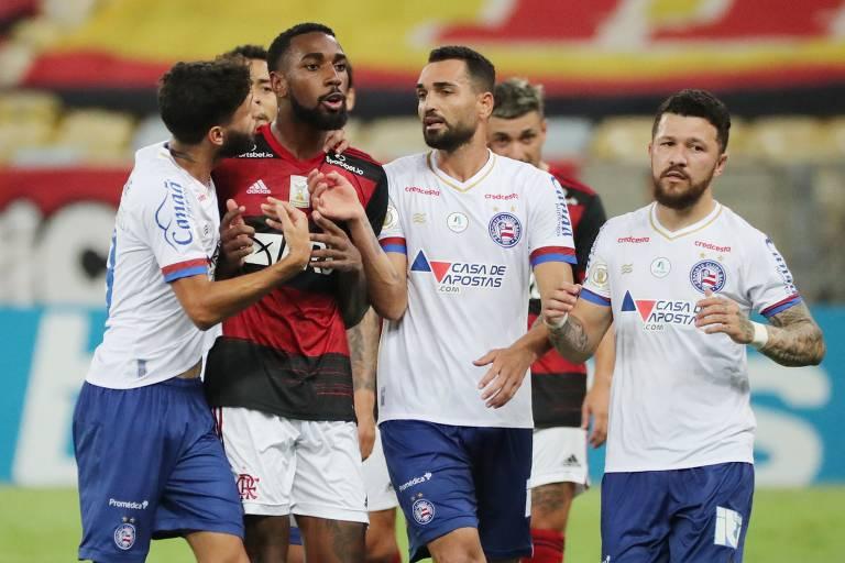 Homem com blusa vermelha e preta é segurado por quatro outros homens, de branco