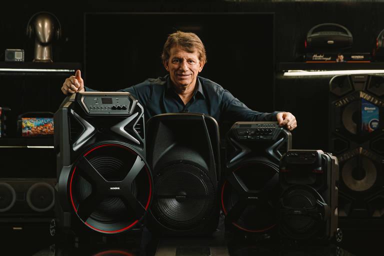 Homem branco segura caixas de som pretas
