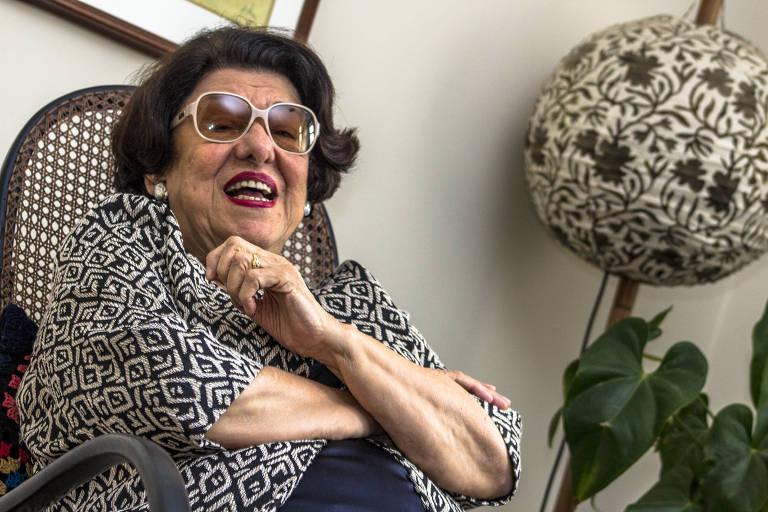 A escritora está bem sorridente, sentada em uma cadeira e usando óculos enormes