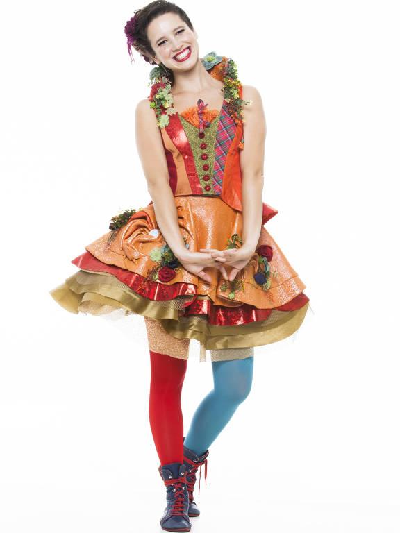 Vestida com saia cheia de badados e uma meia vermelha e outra azul, a artista sorri para a câmera