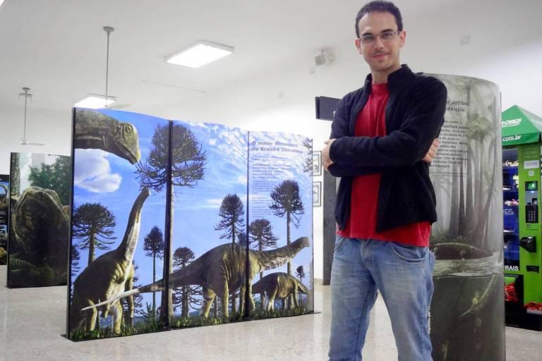 imagem mostra homem de camiseta vermelha e de braços cruzados, com painéis com ilustrações de dinossauros ao fundo