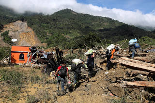 FILE PHOTO: Residents carry their belongings recovered from their houses damaged by a mudslide, caused by heavy rains brought by Storm Eta, as the search for victims continue in the buried village of Queja
