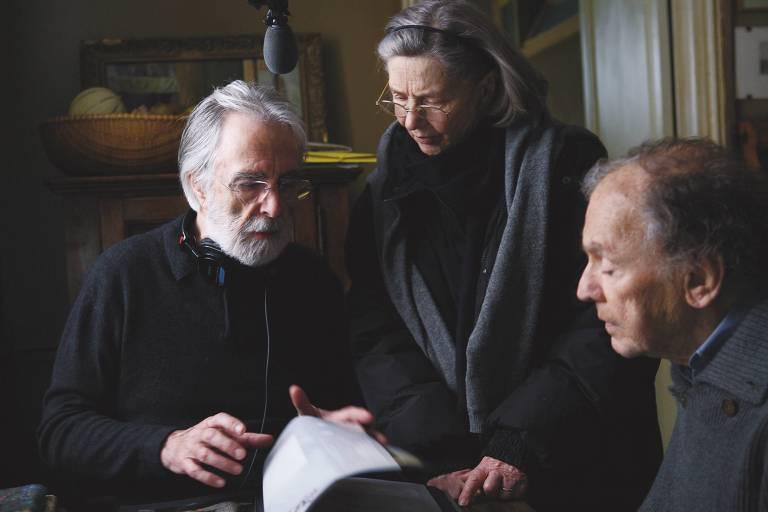 três homens idosos vestidos de preto conversam olhando para um roteiro
