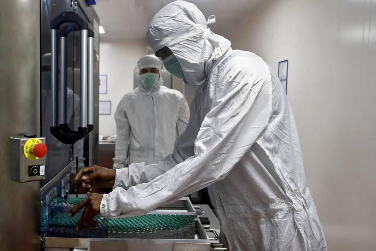 Funcionário manipula vacinas da AstraZeneca/Oxford no Serum Institute of India, em Pune, na Índia