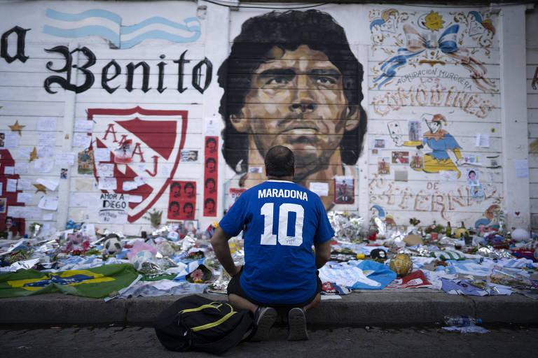 Homem com camisa azul, de costas, ajoelhado em calçada; no muro há o rosto de maradona pintado
