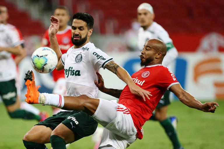 Luan, do Palmeiras, disputa a bola com Patrick, do Internacional, durante confronto entre as duas equipes no sábado (19)