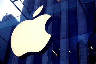FILE PHOTO: FILE PHOTO: The Apple Inc logo is seen hanging at the entrance to the Apple store on 5th Avenue in New York
