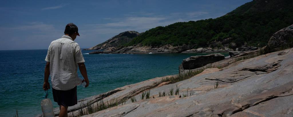 Homem caminha de costas por uma pedra, com mar azul e morro verde ao fundo