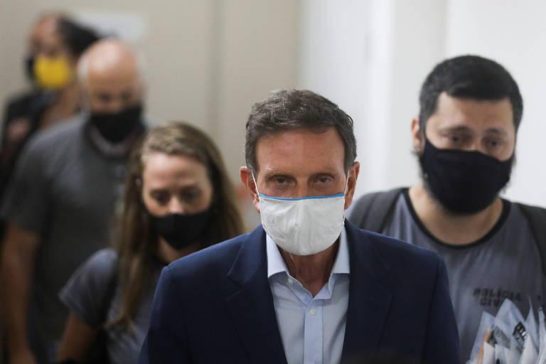 Prefeito do Rio de Janeiro, Marcelo Crivella, de máscara, é conduzido por policiais