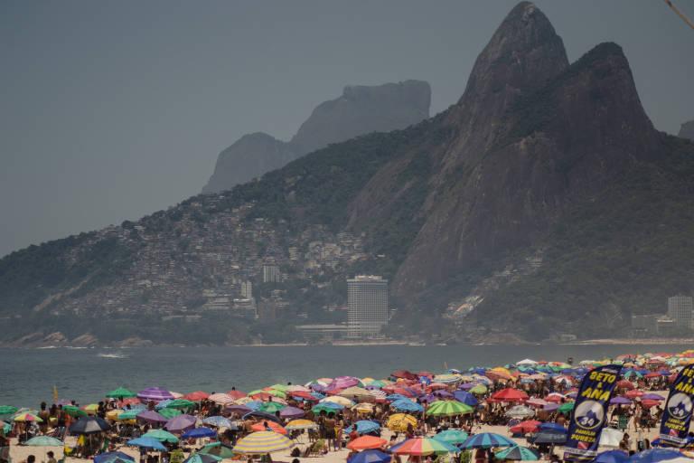Praia cheia no domingo de sol na zona sul do Rio de Janeiro