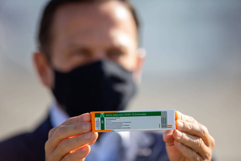 Doria segura caixa da Coronavac, já com o rótulo do Butantan, durante chegada de lote da vacina a SP