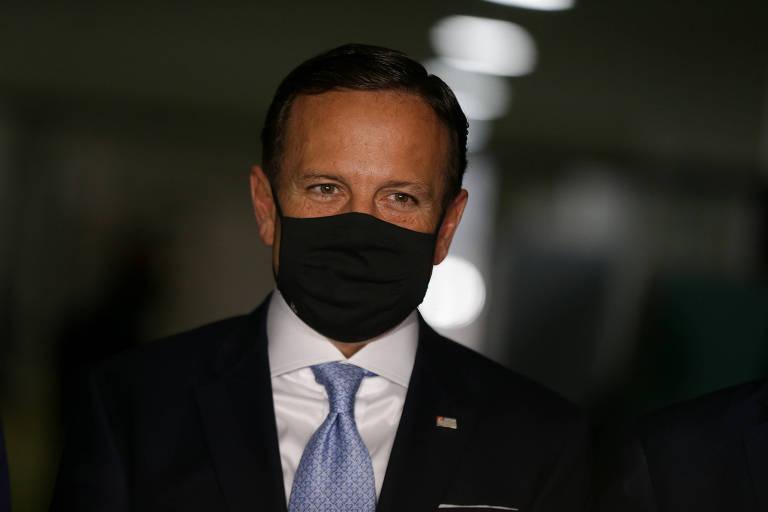 Homem branco veste terno, gravata e máscara de proteção contra o coronavírus