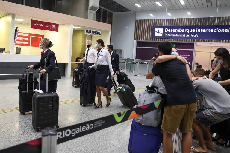 Passageiros e tripulantes de voo da companhia aérea British Airways desembarcam no aeroporto do Galeão, no Rio de Janeiro, na segunda (21)