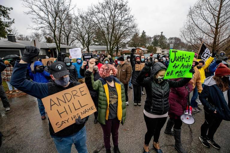 """pessoas vestidas com roupas de inverno levantam as mãos com os punhos fechados e carregam cartazes com os dizeres, em inglês: """"Maurice Hill, say his name"""" e """"Justiça para Andre Hill"""""""