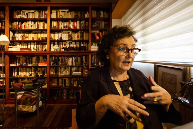 Margareth Dalcomo, mulher de meia idade, usando óculos e cabelos curtos, está sentada de costas para uma grande estante de livros, gesticulando enquanto fala, à luz de um abajur