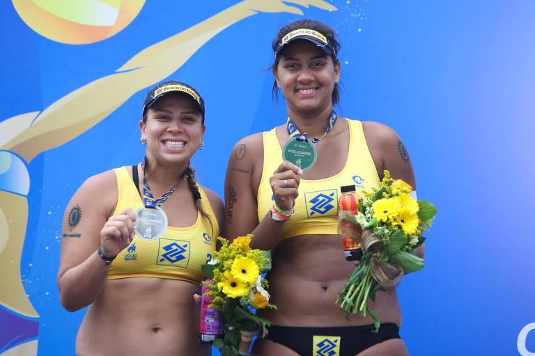 Duas mulheres com top e viseira seguram medalhas