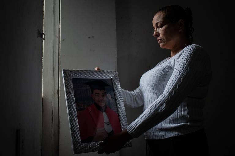 Mulher segura retrato de adolescente de beca, na formatura, olhando com pesar