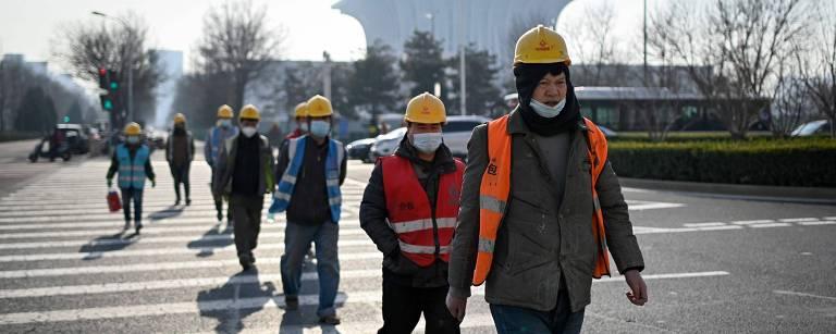 Um grupo de trabalhadores usando máscaras faciais atravessa uma rua em Pequim em 27 de dezembro de 2020