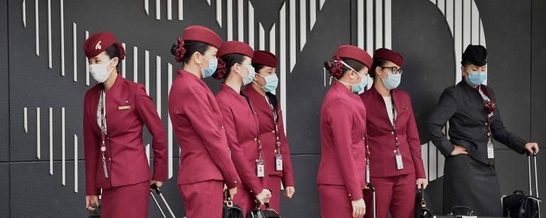 Tripulação da Qatar Airways se prepara para entrar no aeroporto internacional de Sydney, em meio à pandemia de coronavírus