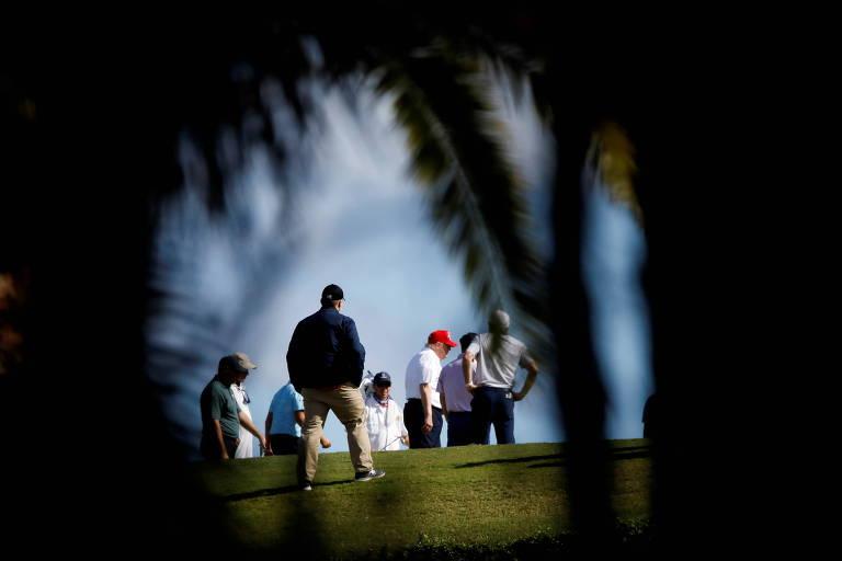 O presidente dos EUA, Donald Trump (de boné vermelho), joga golfe em West Palm Beach, na Flórida, neste domingo (27)