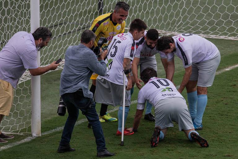 Bolsonaro, de quatro, é cercado por quatro outros jogadores, um fotógrafo e uma pessoa com um celular, logo em frente ao gol, instantes após marcar