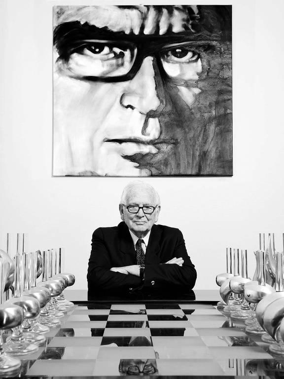 Homem branco em mesa em frente a quadro