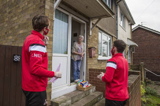 The Doncaster Rovers players Tom Anderson, left, and Jon Taylor deliver a Christmas basket to Doncaster Rover?s fan Lynn Mcfatter on Dec. 8, 2020, in Doncaster, England. (Elizabeth Dalziel/The New York Times)