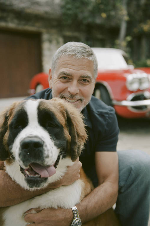 Homem branco sorri e abraça cachorro grande e peludo