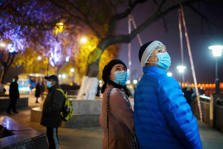 Em rua iluminada à noite, duas pessoas de máscara caminham de mãos dadas, olhando para cima
