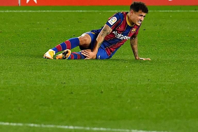 Philippe Coutinho caído no gramado com expressão de dor