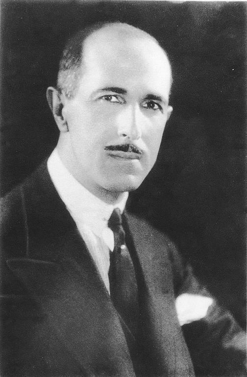 Homem branco calvo, com cabelos ralos e grisalhos nas têmporas e bigode fino, vestido com terno escuro, camisa branca e gravata escura, com um lenço branco na lapela.