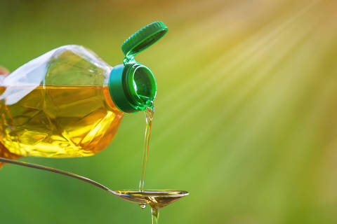 Hand pouring Vegetable oil from bottle to spoon with nature background