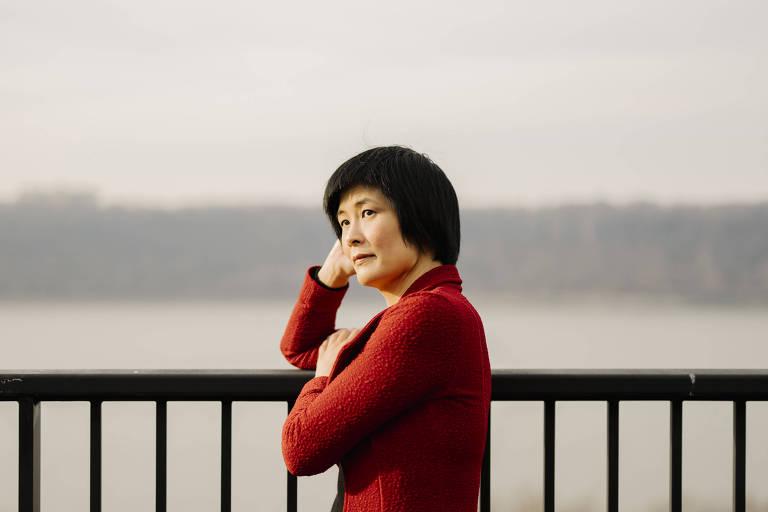 Mulher oriental usa casaco vermelho e apoia braços em uma grade na rua