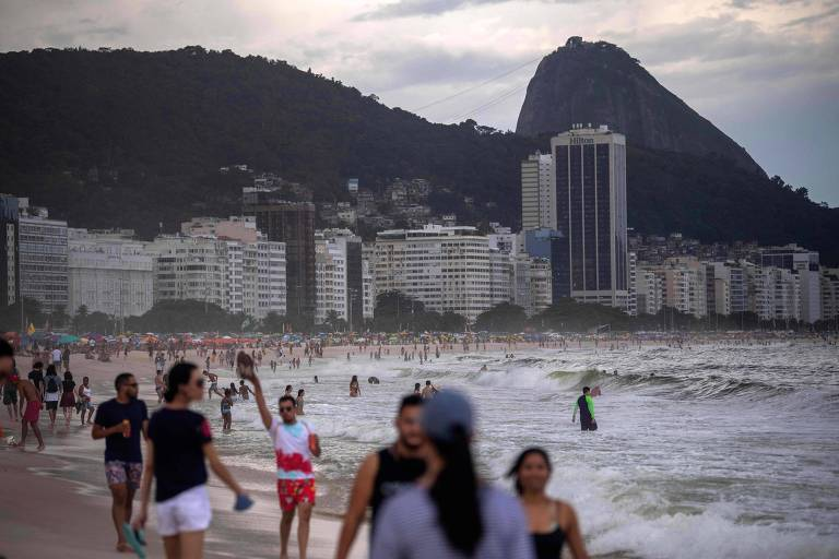 Pessoas caminham na praia de Copacabana, no Rio de Janeiro, em meio a pandemia da Covid-19