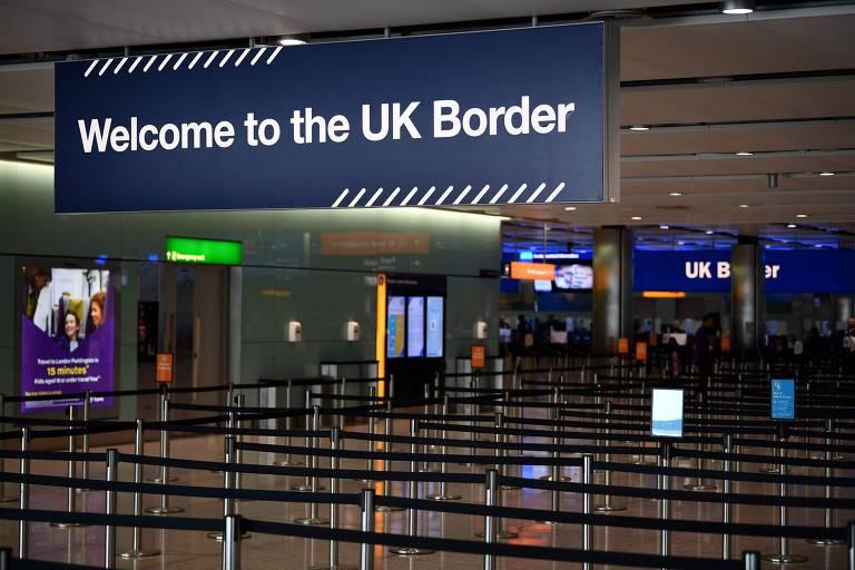 """Placa diz """"bem vindo à  fronteira do Reino Unido"""" em saguão vazio de aeroporto"""