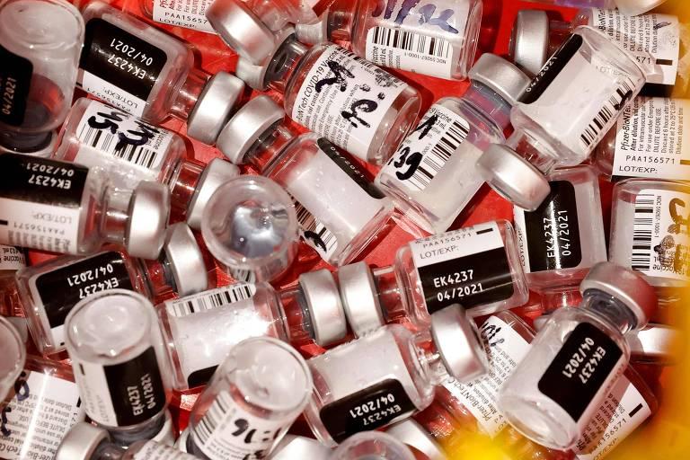 vários vidros de vacina com rótulo preto e branco sobre fundo vermelho