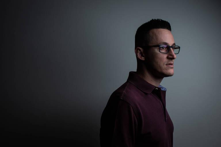 Homem de óculos e cabelo curto olhando para o lado