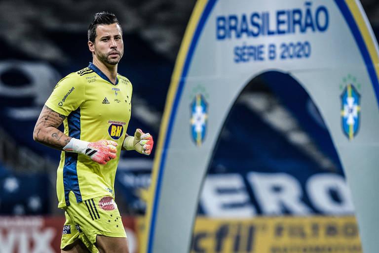 """Fábio, com uniforme amarelo, passa por placa com a inscrição de """"Brasileirão Série B"""""""