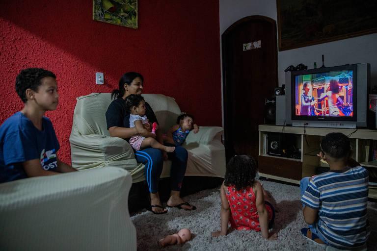 Sheilla Gardenia César com os filhos em sua casa na zona leste; todos veem televisão