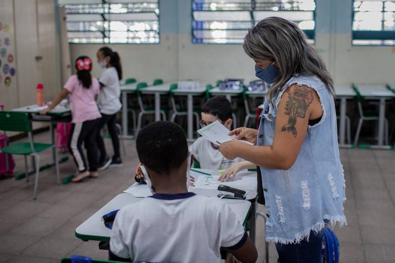 A professora Rizomar Maria Menezes atende aluno na escola municipal Brigadeiro Correia de Mello, na zona leste