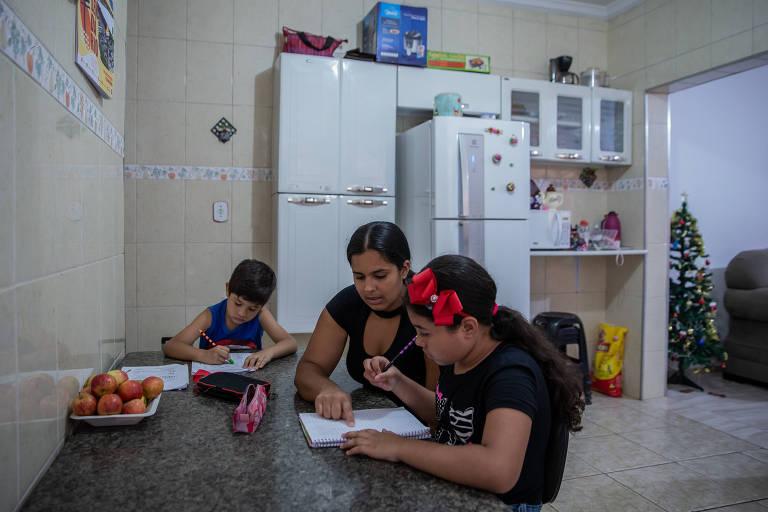Erika Moraes de Sousa Ferraz ajuda os filhos Bruno e Beatriz a estudarem em casa