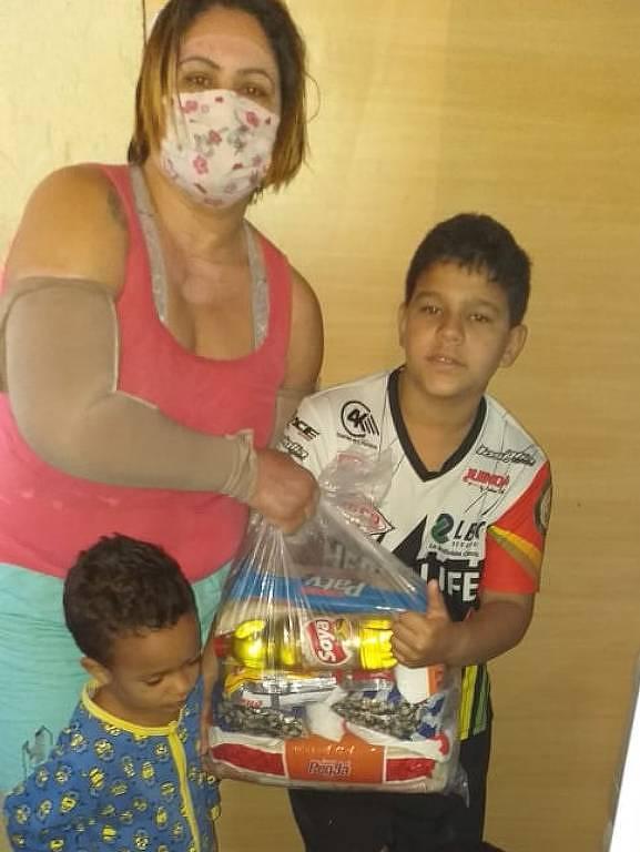 Alessandra Ferreira da Silva com os filhos e cesta do programa Ação contra o Corona