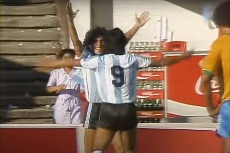 Maradona ergue os braços e é abraçado por um companheiro