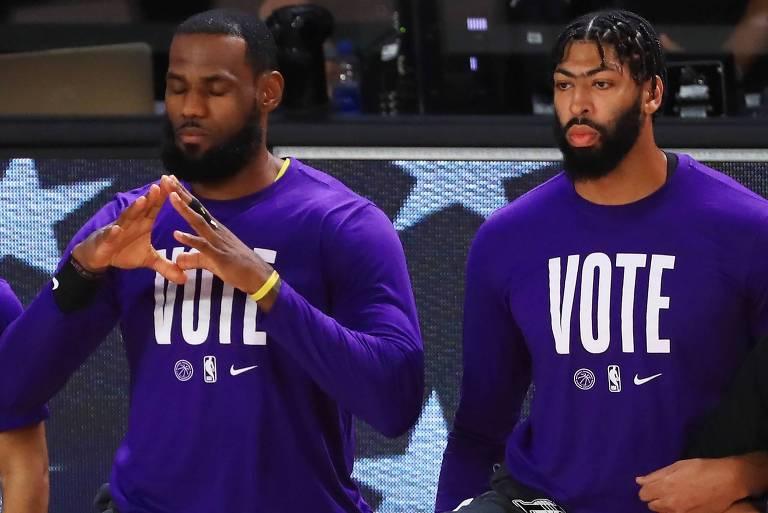 LeBron James (à esq.) e Anthony Davis, do Los Angeles Lakers, se ajoelham durante o hino americano em protesto pelas mortes de cidadãos negros pela polícia do país